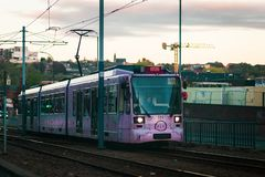 Sheffield, UK - 20th October 2018: One of Sheffields new Pink trams runs through the city. A single tram running through the city at sunset in Autumn royalty free stock images