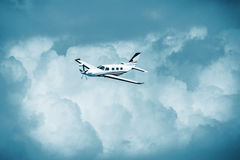 Single turboprop aircraft.. Small private plane flying in blue clouds. Royalty Free Stock Photo