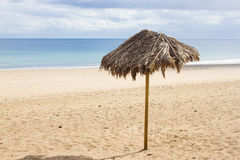 Single umbrella on lonely beach. Isolates parasol on Canary beach with beautiful sand Stock Photos