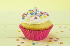 Single vanilla sponge birthday cupcake frosted Stock Images