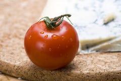 Single vine tomato. A single fresh vine tomato with water droplets on cork board Stock Photography