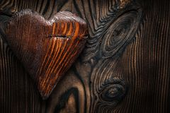 Single vintage wood valentine toy heart on wooden board royalty free stock photography