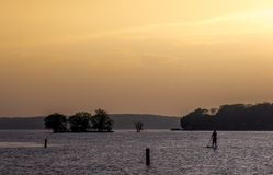 Single wake boarder lake at sunset. Silhouette of a wake boarder at sunset Royalty Free Stock Image