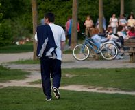 Single Walker. Adult man walking in the park and dozen of people in blur background Stock Image