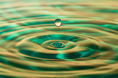 A single water drop and waves. Water drop and waves on water with green background Stock Photography