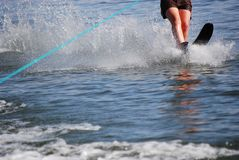 Single water ski. Legs and ski line of an individual skiing on one ski Stock Images