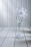 Single wedding ornated empty wineglass standing on white wooden Stock Image
