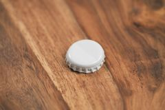 Single white beer bottle cap on wood table Stock Image
