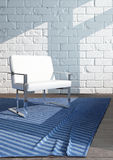 Single white chair standing on blue carpet Stock Photos