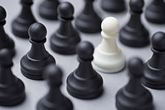 Single white chess pawn amongst black ones Stock Photo