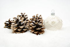 Single white christmas bauble with pine cones on snow isolated Stock Photo