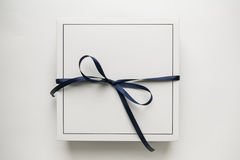 Single white gift paper box with blue ribbon bow, isolated on white background.  Stock Image