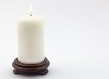 Single white lit candle on white background Royalty Free Stock Image