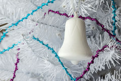 Single white ornamental glass bell on white christmas tree Royalty Free Stock Photography