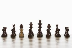 Single white pawn in initial line up of black chess pieces Stock Photo