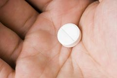 Single white pill in palm Stock Photography