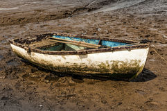 Single white rowing boat stuck on mud flats Stock Images