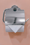 Single white toilet paper roll metallic dispenser mounted on the wall Stock Photography