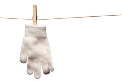 Single white winter glove hanging on a clothesline Royalty Free Stock Image