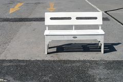 Single white wooden bench is placed in afternoon sunlight on concrete floor of empty car park. There are yellow arrows symbol on back, old wood chair stand royalty free stock images