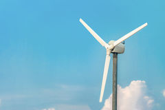 Single wind turbine closeup on the blue sky background. Alternative energy Stock Photography