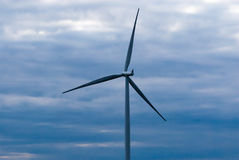 Single wind turbine on dark cloudy sky Royalty Free Stock Photography