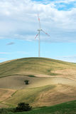 Single wind turbine in farmland on a hilltop. With rolling fields and meadows providing a source of renewable electricity from the conversion of the kinetic Royalty Free Stock Photo