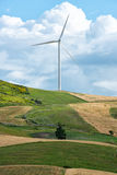 Single wind turbine on top of a rural hill. Single wind turbine providing renewable energy on top of a rural hill with agricultural fields and meadows below Royalty Free Stock Photo