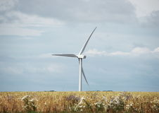 Single windmill in grass field with clouds Stock Photo