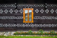 Single window in decorative wall in Cicmany. Cicmany, Slovakia - august 02, 2015: Old wooden houses in Slovakia village Cicmany, traditional painted with white Stock Photo