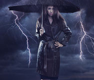 Single woman. Wearing coat holding umbrella. Creative szmbol of the bad weather royalty free stock images
