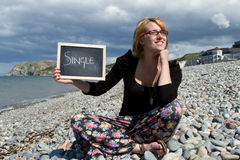 Single woman. A pretty young woman sits on a pebble beach with a sign with the word 'single Stock Image