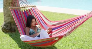 Single woman in bikini reading a book in hammock stock video
