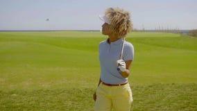 Single woman enjoying sun while playing golf stock video