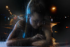Single woman in frustration. Sitting behind the window covered with raindrops. Misfortune concept royalty free stock photos