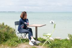 Single woman relaxing on promenade with smartphone on seaside coast beach view. A single woman relaxing on promenade with smartphone on seaside coast beach view royalty free stock images