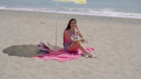 Single woman relaxing under beach umbrella. Single woman in blue jeans shorts with long brown hair relaxing on pink blanket under yellow umbrella at sandy ocean stock footage