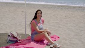 Single woman relaxing under beach umbrella. Single woman in blue jeans shorts with long brown hair relaxing on pink blanket under yellow umbrella at sandy ocean stock video