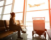 Single woman sitting in airport terminal and passanger plane fly. Ing outdoor for traveling theme stock images