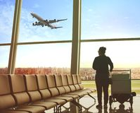 Single woman sitting in airport terminal and passenger plane fly. Ing outdoor for traveling theme royalty free stock photo