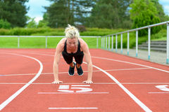 Single woman stretching calf muscles at race track stock image
