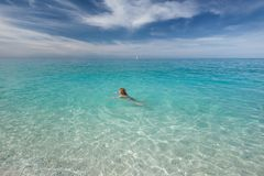 Single woman swimming in the transparent sea at idyllic day Stock Photography