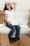 Single Woman Tired Unpacking Boxes Moving House. A beautiful single young woman tired and exhausted while packing or unpacking boxes and moving into a new home stock photo