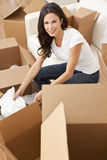 Single Woman Unpacking Boxes Moving House. A beautiful single young woman unpacking boxes and moving into a new home Royalty Free Stock Image