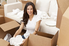 Single Woman Unpacking Boxes Moving House. A beautiful single young woman unpacking boxes and moving into a new home stock photo
