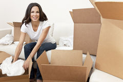 Single Woman Unpacking Boxes Moving House. A beautiful single young woman unpacking boxes and moving into a new home Stock Images