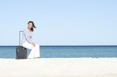 Single woman waiting with case at seaside Stock Photography