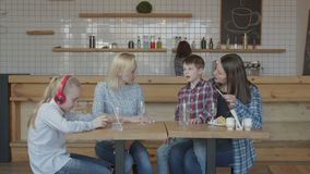 Single women with kids spending leisure in cafe. Two adult mothers enjoying leisure with preadolescent children while sitting at cafe table. Caring woman feeding stock video footage