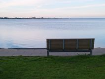 Single wooden bench in front of the sea Stock Photos