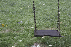 Single wooden children swing set hanging still in a park Royalty Free Stock Photo